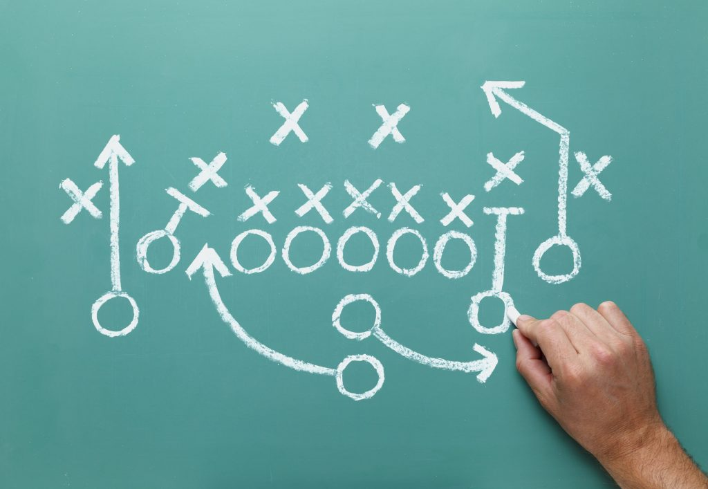 38258047 - football play drawn on green chalk board with hand.