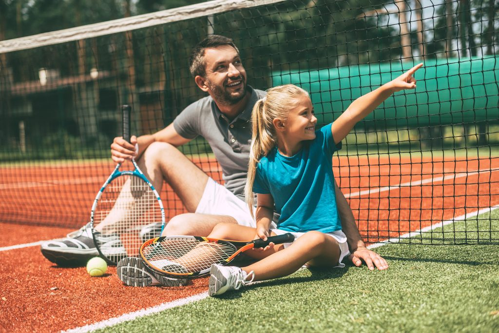 Cheerful father and daughter leaning at the tennis net and looking away with smiles while both sitting on tennis court