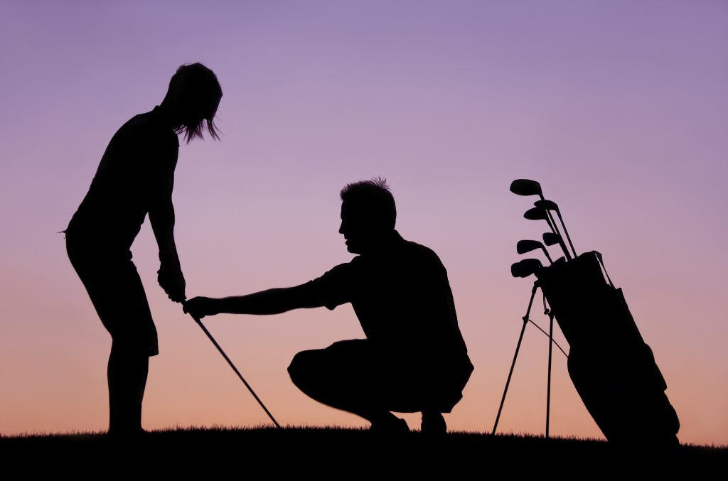 A silhouette of a woman getting a golf lesson from a golf professional and instructor. Themes of the image include golf lessons, instruction, short game, sport, game, practice, teaching, learning, lesson tee, driving range, golf professional, chipping, evening, model, young, woman, attractive, side view, 30s, helping, assisting, and golf academy.